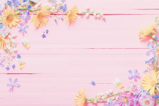 Рамка из красивых цветов на розовом фоне деревянных