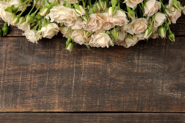 茶色の木製テーブルの上の美しいミニバラのフレーム