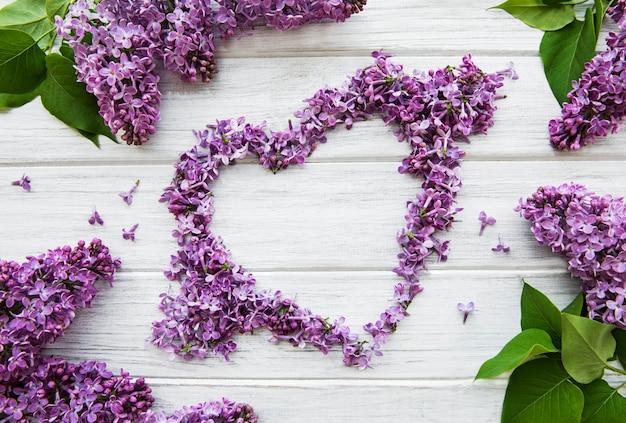 ハートの形をしたテーブルの上のライラックの枝と花のフレーム、トップビエフ、フラットレイ、イースター、母の日、女性の日のコピースペース