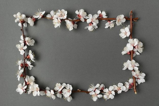 灰色の背景に花と枝のフレーム。テンプレート。背景。モックアップ。