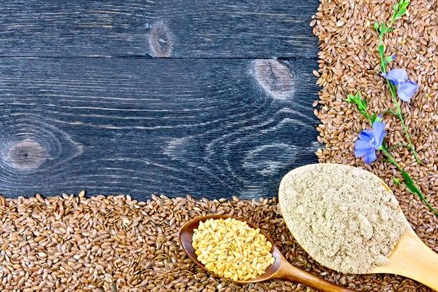 茶色と白の亜麻仁のフレーム、スプーンでリネン粉、黒い木の板の背景に青い亜麻の花
