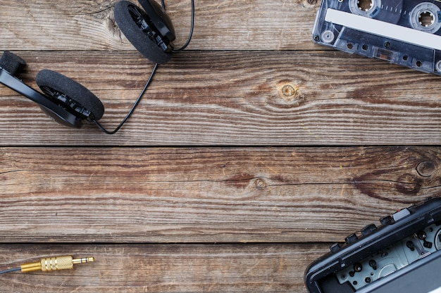 木製のテーブルの上にカセットテープ、カセットプレーヤー、ヘッドフォンのフレーム。上面図。テキスト、ロゴなどのための空きスペースを持つレトロなコンセプト。