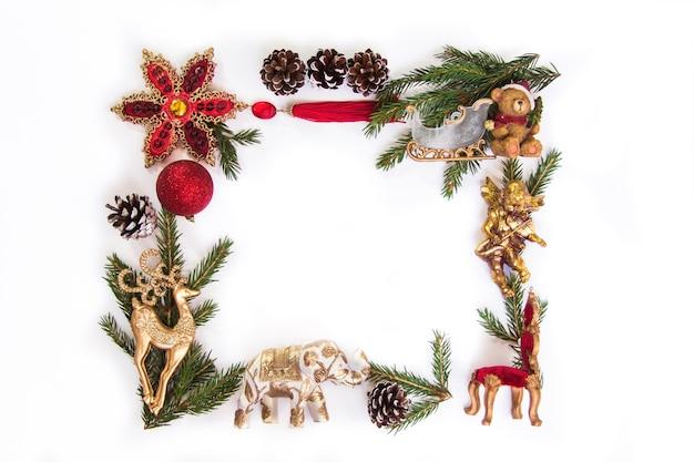 クリスマスツリーのフレームは、白い背景の上の赤と金の装飾を分岐しますフラットレイコピースペース