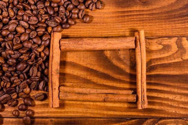 Рамка из палочек корицы, кофейных зерен и звездчатого аниса на деревенском деревянном столе