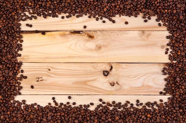 밝은 나무 배경에 커피 콩의 프레임입니다. 복사 공간이있는 평면도