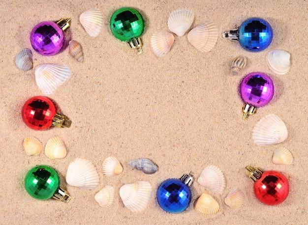 カラフルなクリスマスの装飾とビーチの砂の貝殻のフレーム
