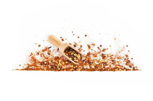 砕いた赤カイエンペッパー、赤唐辛子パプリカ、乾燥唐辛子フレーク、種子、白で分離された木製スクープのフレーム