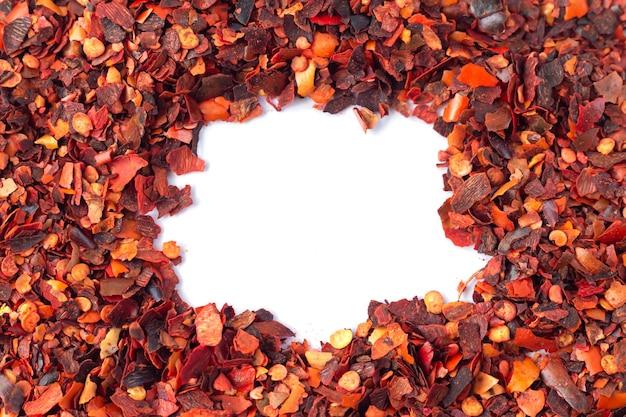 砕いた赤唐辛子のフレーム、コピースペースで白い背景に分離された乾燥カイエンペッパーフレーク