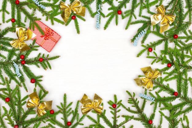 흰색 나무 배경에 빨간색 선물 상자가 있는 장식된 녹색 크리스마스 나무 가지 프레임
