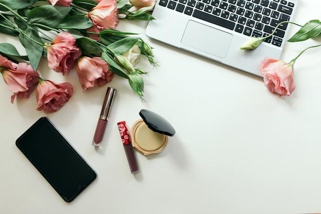 装飾的な女性の化粧品とトルコギキョウの花、トップビューでジュエリーのフレーム。白い壁にフラットレイアウトのフラワーアレンジメント