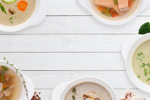 白い木製のテーブルの上のさまざまなスープのフレーム