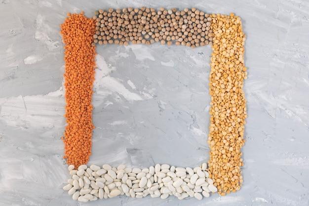 말린 된 병아리 콩, 렌즈 콩, 말린 완두콩, 회색 테이블에 병아리 콩, 상위 뷰 음식의 프레임