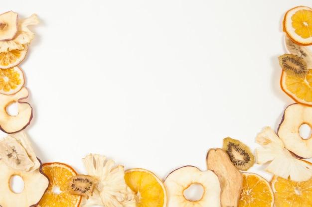 Кадр из сухофруктов апельсина, банана, яблока, киви, ананаса и груши на белом фоне вид сверху