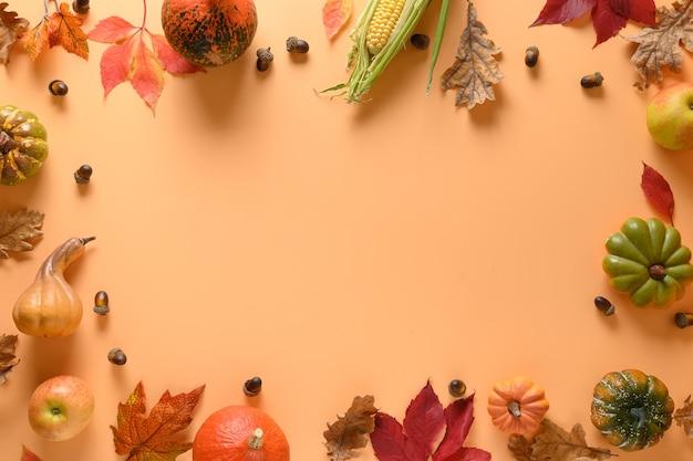 秋の収穫のフレーム、カボチャ、オレンジ色の背景にカラフルな葉。感謝祭とハロウィーン。
