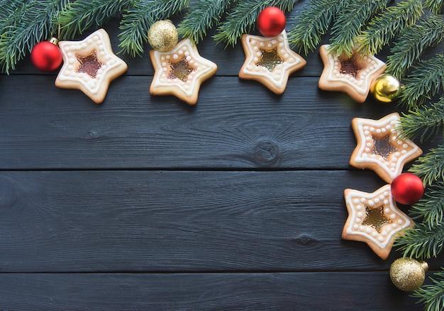 나무 테이블 표면에 전나무 가지 빨간색과 금색 크리스마스 트리 볼과 쿠키의 프레임