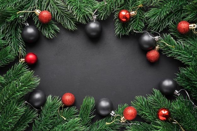 黒のマットな背景にクリスマスの赤と黒のボールとモミの枝のフレーム。