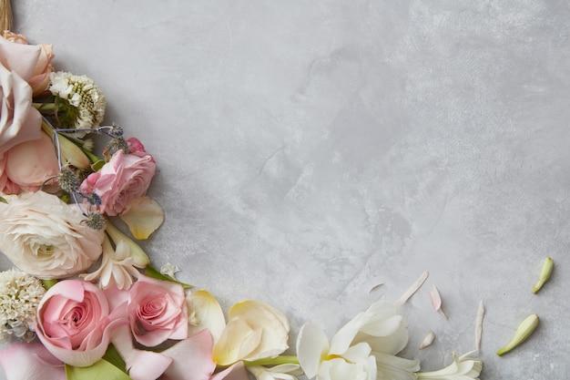 회색 배경을 장식하는 꽃의 프레임입니다. 회색 배경을 디자인하는 흰색, 분홍색 장미 구성의 상위 뷰. ns