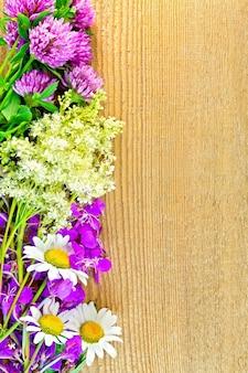 木の板の背景にクローバー、カモミール、ファイアウィード、メドウスイートの花のフレーム