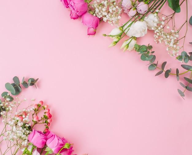 テキスト用の空白スペースとピンクの背景の花のフレーム。上面図、フラットレイ。