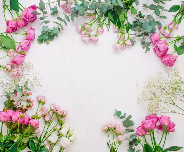 テキスト用の空白のスペースと白い大理石の背景に花のフレーム。上面図、フラットレイ。