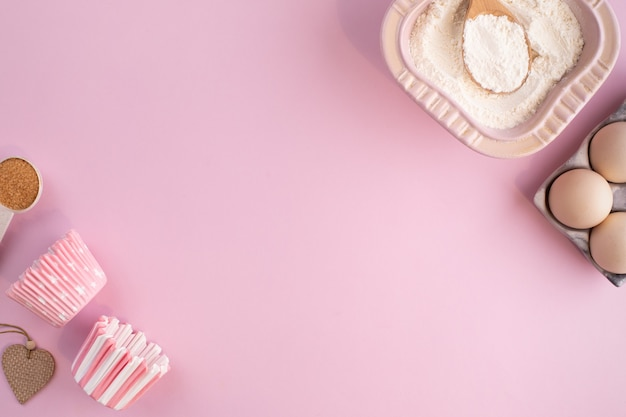 부드러운 분홍색 파스텔 표면에 베이킹하기위한 음식 재료의 프레임
