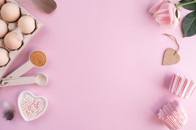 やさしくピンクのパステルテーブルで焼くための食材のフレーム。コピースペースのあるフラットレイを調理します。上面図。ベーキングの概念。フラットレイ