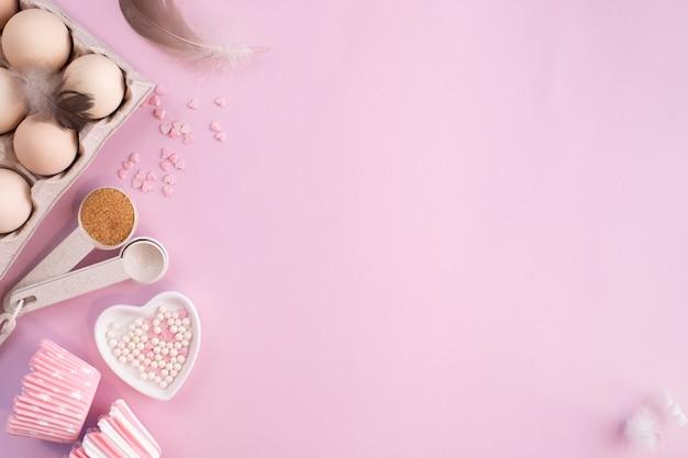 부드러운 핑크 파스텔 테이블에 베이킹을위한 음식 재료의 프레임. 복사 공간으로 평평하게 누워 요리. 평면도. 베이킹 개념. 평평하다