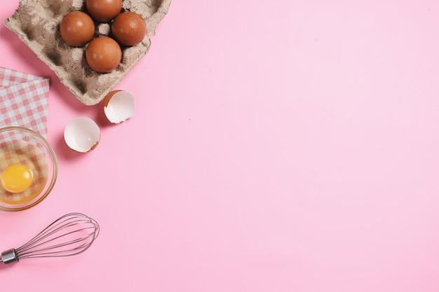 赤ちゃんピンクの背景にベーキング用品と食材のフレーム