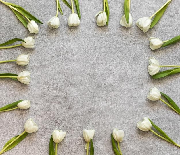 Рама из свежих тюльпанов на старом каменном фоне.