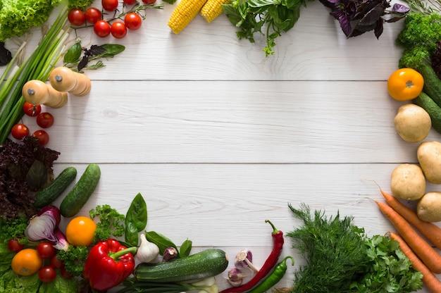 Рамка из свежих овощей на белом дереве с копией пространства