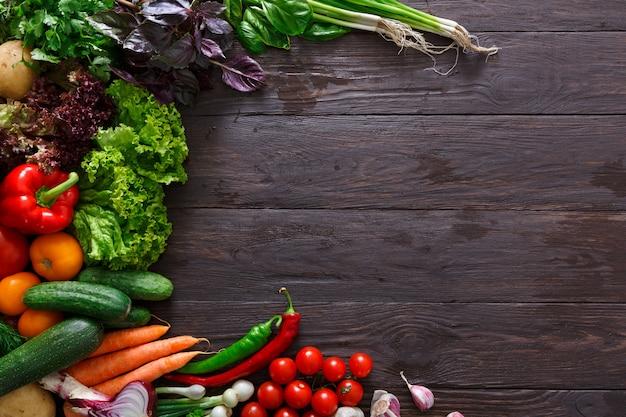 コピースペースを持つ木製の背景での新鮮野菜のフレーム