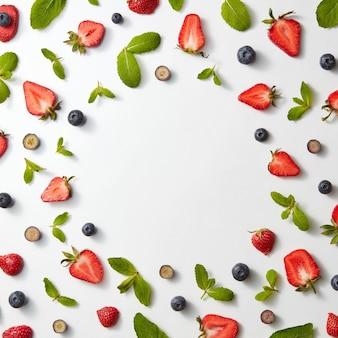 白い背景、フラットにイチゴ、ブルーベリー、ミントの葉とフルーツパターンのフレーム
