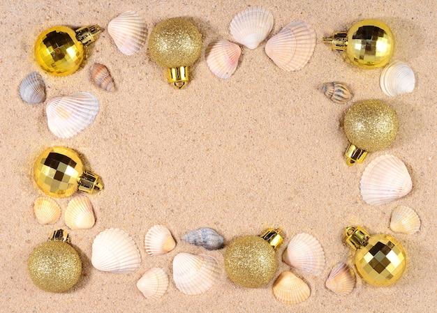 ビーチの砂の上の黄金のクリスマスの装飾と貝殻のフレーム