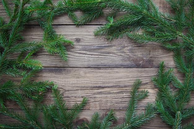 Рамка из зеленых веток елки на деревенском деревянном фоне с копией пространства