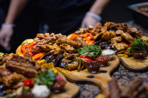 グリルステーキ、グリル野菜、ポテト、サラダ、さまざまなスナック、自家製レモネードのフレーム、上面図。コンセプトディナーテーブル。