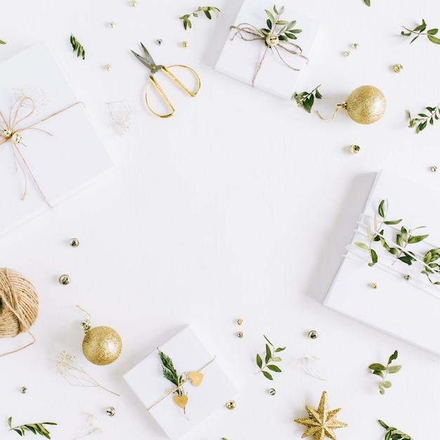手作りのクリスマス ギフト ボックスと白い背景のお祝いの装飾のフレーム。フラットレイ、トップビュー