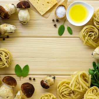 パスタを調理するための食材のフレーム。ポルチーニ茸、チーズ、セージのフェットチーネは、木製の背景に残します。