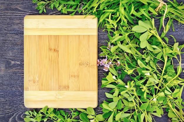 木製のテーブルの背景にフェヌグリーク、rue、セイバリー、タラゴン、タイム、長方形のボードの葉のハーブのフレーム