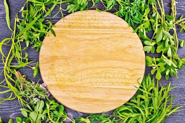 フェヌグリーク、rue、セイボリー、タラゴン、タイム、木製のテーブルを背景に丸いボードの葉のハーブのフレーム