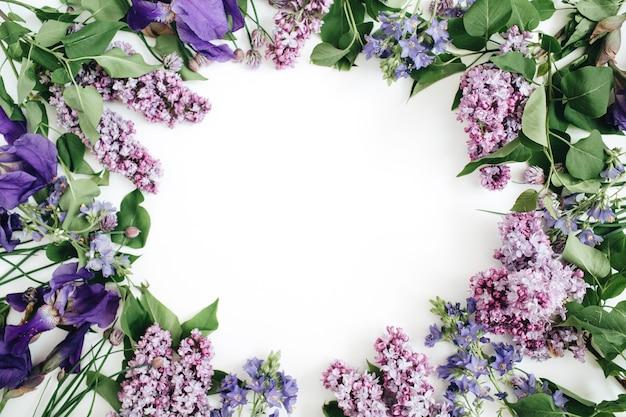 ライラックの花、枝、葉、花びらのフレームで、白い背景にテキスト用のスペースがあります。平置き
