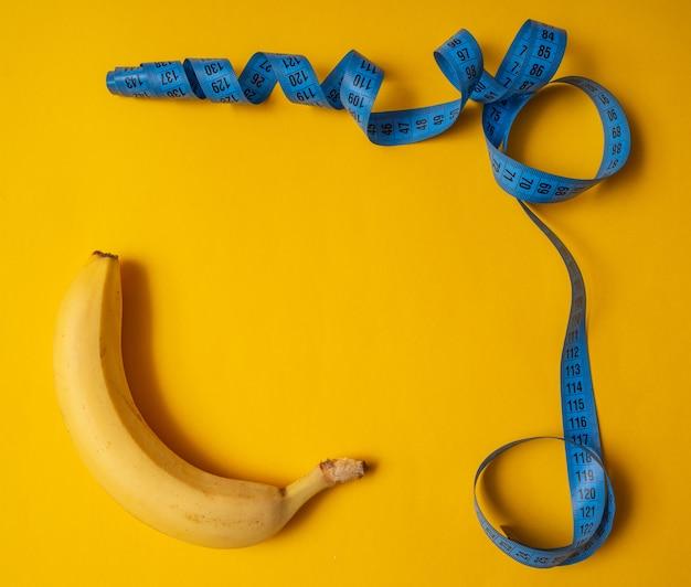 測定テープと黄色の背景にバナナのフレーム。コピースペース、フラットレイアウト。フィットネスの概念。
