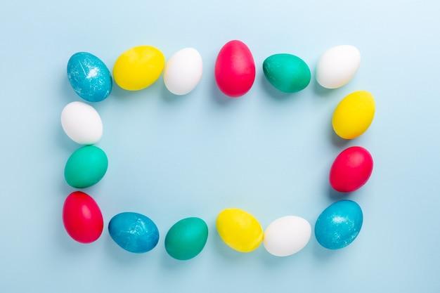 Рамка из разноцветных пасхальных яиц на синем фоне. пасхальная композиция. скопируйте пространство. мокап - изображение