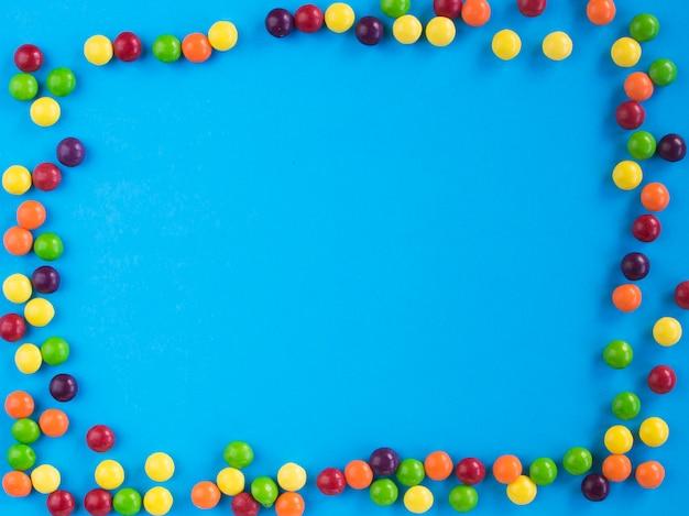 파란색 배경 복사 공간에 여러 색상의 작은 사탕 프레임이 있는 텍스트 평면 평면 보기