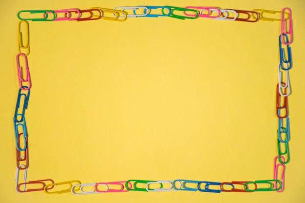 노란색 배경 배경에 고립 된 텍스트에 대 한 여러 다채로운 종이 클립의 프레임