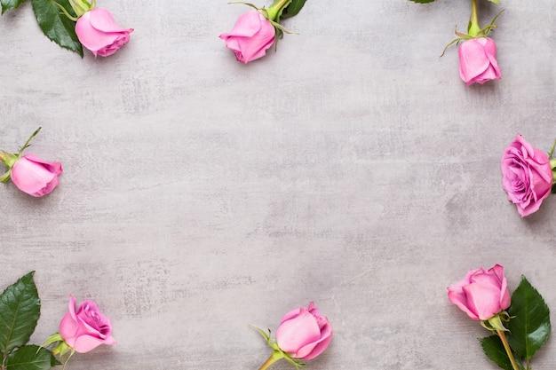 灰色の背景にピンクのバラのフレーム。フラットレイ、上面図