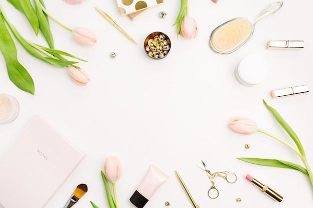 ピンクのチューリップの花、アクセサリー、化粧品のフレーム。女性のホーム オフィス デスクのモックアップ。フラットレイ、トップ ビュー