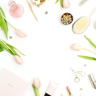 白い背景にピンクのチューリップの花、アクセサリー、化粧品のフレーム。ホーム オフィス デスクのモックアップ。フラット レイアウト、トップ ビュー。