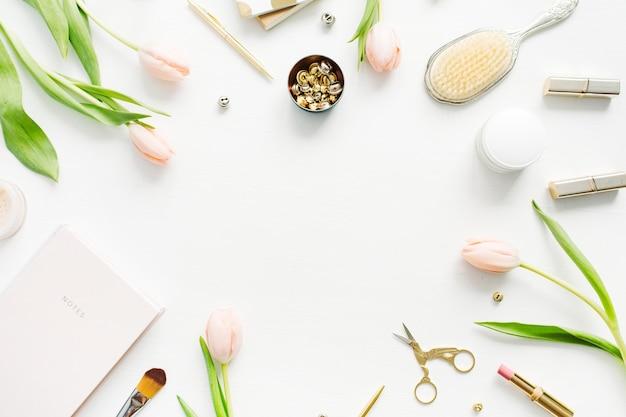 ピンクのチューリップの花、アクセサリー、化粧品のフレーム。女性のホーム オフィス デスクのモックアップ。フラットレイ、トップビュー