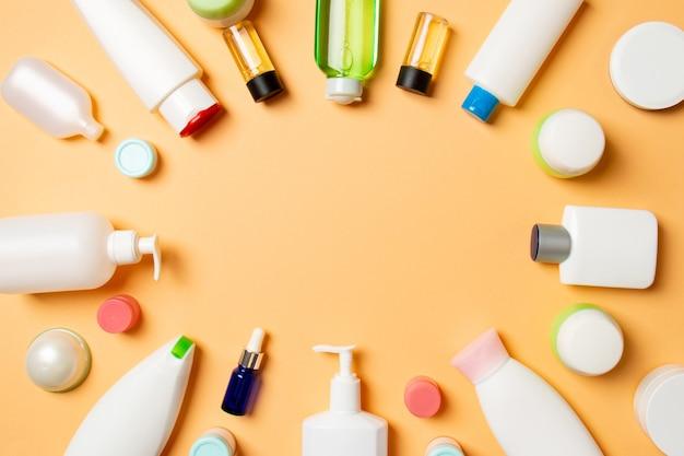 プラスチック製のボディケアボトルのフレームあなたがデザインするための着色された表面の空きスペースに化粧品を含むフラットレイ組成物