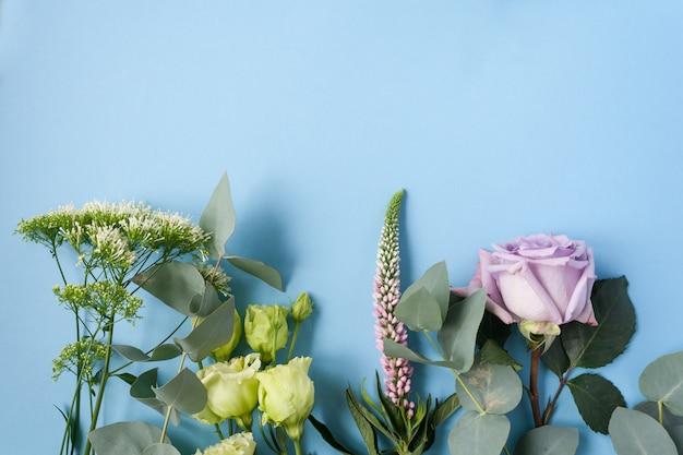 Рамка из фиолетовых и розовых роз, белых лизиантусов и разных цветов на синем фоне.
